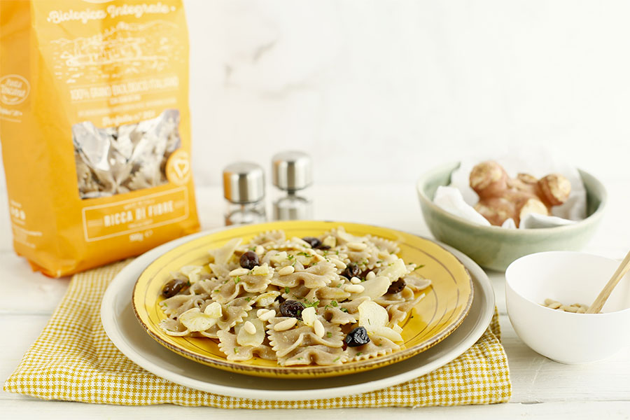 Farfalle with topinambur, taggiasche olives and pine nuts